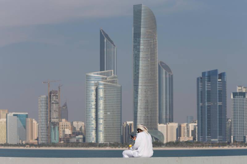 Abu Dhabi, United Arab Emirates, February 8, 2017:    An Emirati man uses his smartphone while drinking coffee on the breakwater along the corniche in Abu Dhabi on February 8, 2017. Christopher Pike / The National  Job ID:  Reporter:  N/A Section: News Keywords: possible focal point *** Local Caption ***  CP0208-Na-standalone-03.JPG