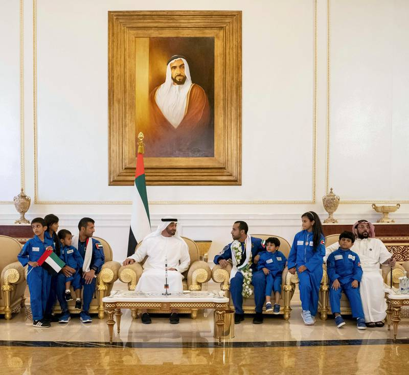 ABU DHABI, UNITED ARAB EMIRATES - October 12, 2019: HH Sheikh Mohamed bin Zayed Al Nahyan, Crown Prince of Abu Dhabi and Deputy Supreme Commander of the UAE Armed Forces (6th R), receives Hazza Ali Al Mansoori, the first UAE Astronaut to be deployed on a space mission to the International Space Station (ISS) (5th R), and Sultan Saif Al Neyadi, a member of the International Space Station mission back-up team (7th R), during a home-coming reception at the Presidential Airport.   ( Hamad Al Kaabi / Ministry of Presidential Affairs ) ---