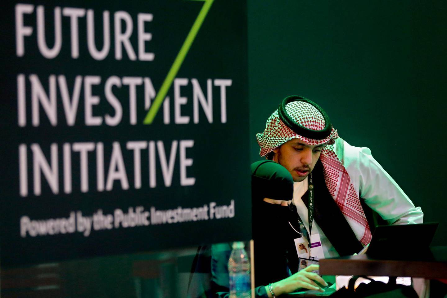 FILE - In this Oct. 22, 2018, file photo, Saudi employees print badges of participants of the Future Investment Initiative in Riyadh, Saudi Arabia. Lured by a long-looming stock offering of Saudi Arabia's massive state-run oil company, investors and business leaders have returned to the kingdom's capital for an investment forum overshadowed last year by the assassination of Washington Post columnist Jamal Khashoggi. (AP Photo/Amr Nabil, File)