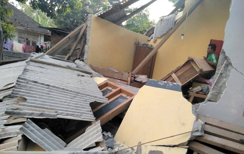 In this image made from video released by Indonesia's Disaster Mitigation Agency, a man inspects the damage caused by an early morning earthquake on the island of Lombok, Indonesia, Sunday, July 29, 2018. A shallow magnitude 6.4 earthquake early Sunday killed a number people and injured dozens on Indonesia's Lombok Island, a popular tourist destination next to Bali. (Indonesia's Disaster Mitigation Agency via AP)