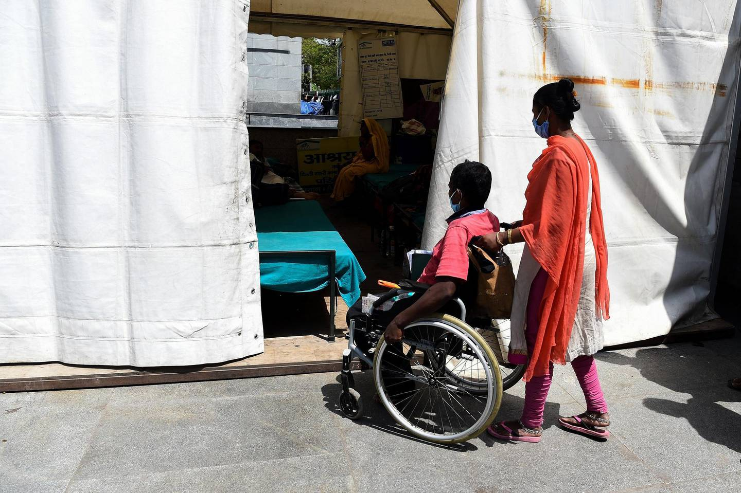 This photograph taken on April 7, 2020 shows wife of 38-year-old patient Upender Safi (C) pushing his wheelchair at a night shelter setup by Delhi government outside the All India Institute of Medical Sciences (AIIMS) during a government-imposed nationwide lockdown as a preventive measure against the COVID-19 coronavirus, in New Delhi. - The capacity of medical facilites around the world has been stretched by the surge of COVID-19 patients as outbreaks worsen in many countries. It can cause people with other life-threatening diseases to miss out on vital care -- especially in places like India, where healthcare systems are shakier. Dozens of people with serious medical conditions are camped outside India's national medical institute in tents set up by the Delhi government. (Photo by Prakash SINGH / AFP) / To go with FOCUS 'HEALTH-VIRUS-INDIA' by AISHWARYA KUMAR.