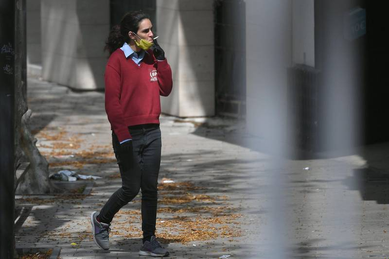 A woman wearing a face mask smokes a cigarette in Vilanova i la Geltru near Barcelona on March 24, 2020 amid a national lockdown to stop the spread of the COVID-19 coronavirus. Spain is Europe's second-hardest hit country by the coronavirus outbreak, with over 33,000 confirmed cases of the disease and 2,182 deaths. / AFP / LLUIS GENE