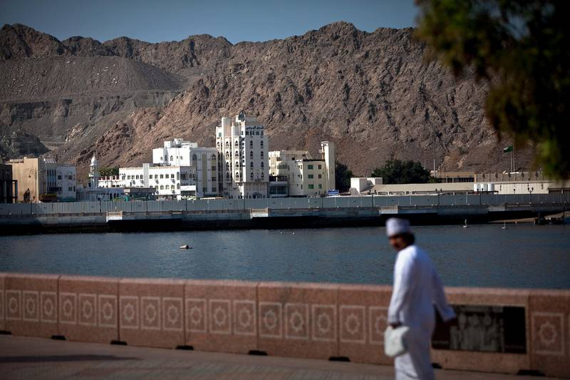 A man walks on the corniche near Mina as Sultan Qaboos Muscat in the Mutrah district in Muscat, the capital of the Sultanate of Oman on Wednesday, Oct. 12, 2011. (Silvia Razgova/The National)