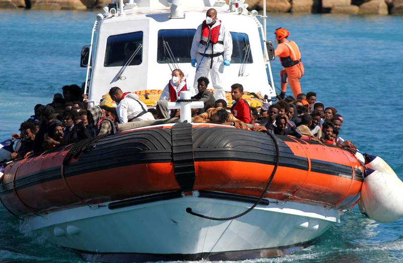 Migrants approach aboard a search-and-rescue boat after hundreds arrive on the southern island of Lampedusa, Italy May 9, 2021. Picture taken May 9, 2021. REUTERS/Mauro Buccarello NO RESALES. NO ARCHIVES