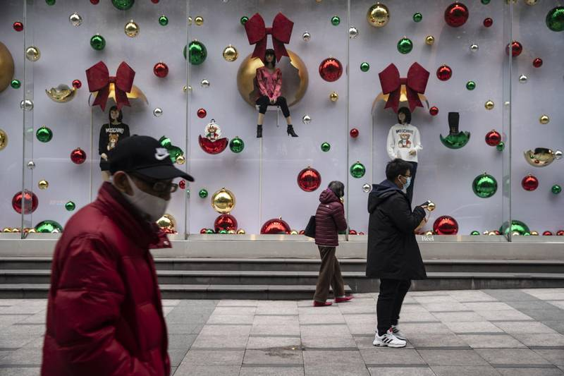 Pedestrians walk past a store window decorated with festive themes in Shanghai, China on Saturday, Dec. 19, 2020. China pulled further ahead of other major economies in November as industrial output and retail sales strengthened, reinforcing expectations of healthy growth in 2021. Photographer: Qilai Shen/Bloomberg