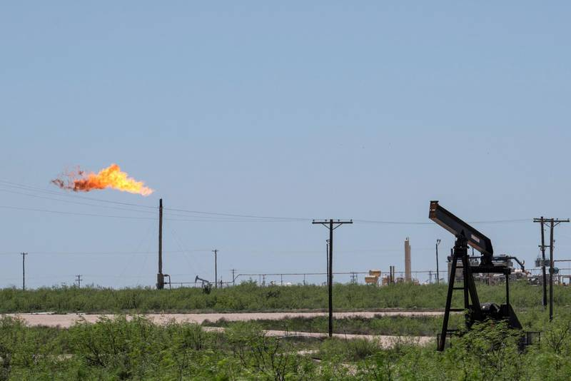(FILES) In this file photo a flare stack is pictured next to pump jacks and other oil and gas infrastructure on April 24, 2020 near Odessa, Texas. Malfunctioning equipment accounts for about half of the biggest sources of potent greenhouse gas methane emissions at the United States' largest oilfield, a study led by NASA showed on June 2, 2021. Researchers found that repairing just 123 sources found to leak most persistently in the area they surveyed using sensor-equipped planes would reduce methane emissions by 55 tons (50 metric tons) an hour. / AFP / Paul Ratje