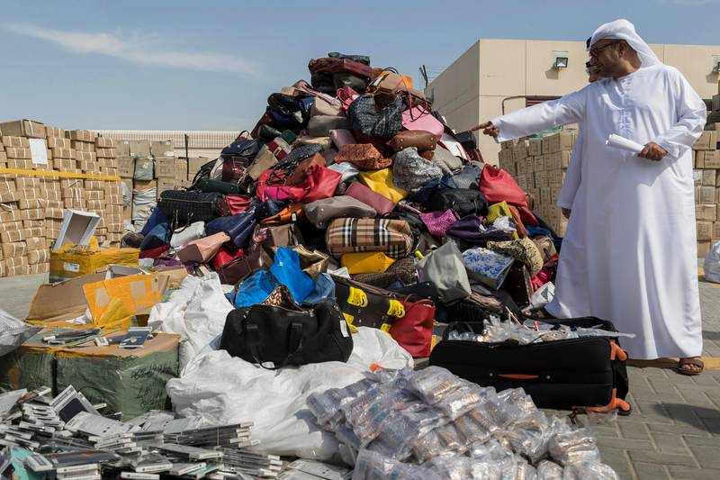 DUBAI, UNITED ARAB EMIRATES, 08 FEBRUARY 2017. Ibrahim Behzad, Director of Intellectual Property Rights Management at DED looks through a pile of counterfeit products at the DED in Al Garhoud. The products are scheduled to be distroyed and recycled. (Photo: Antonie Robertson/The National) ID: 75938. Journalist: Nick. Section: National. *** Local Caption ***  AR_0802_Fake_Goods-09.JPG