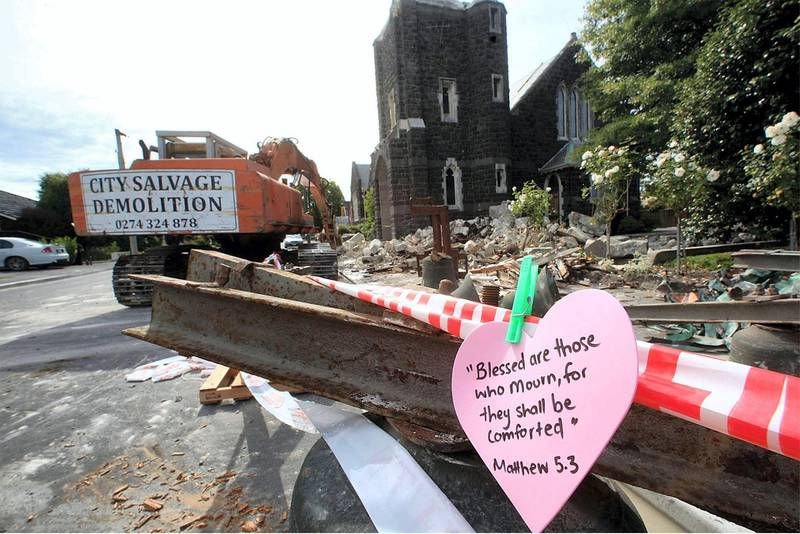 A note displayed outside St. Mary's Church in Papanui as demolition teams prepare to knock down the remains of the bell tower (top) in Christchurch on February 28, 2011, seven days after a 6.3 magnitude earthquake rocked the city. AFP