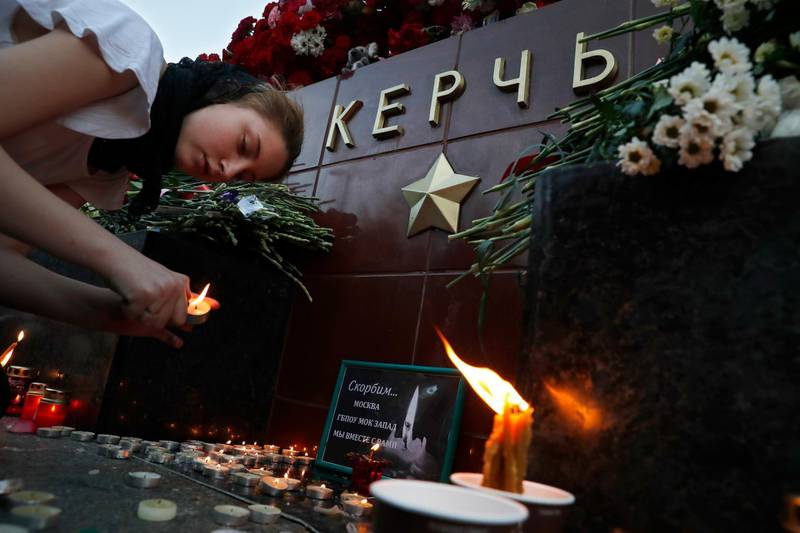 A girl lights a candle in memory of the victims of Wednesday's attack on a vocational college in Kerch, Crimea, at the memorial stone with the word Kerch in the Alexander Garden near the Kremlin, Moscow, Russia, Thursday, Oct. 18, 2018. A top official in Crimea says authorities are searching for a possible accomplice of the student whose shooting-and-bomb attack on his vocational school killed 20 people and wounded more than 50 others. (AP Photo/Pavel Golovkin)