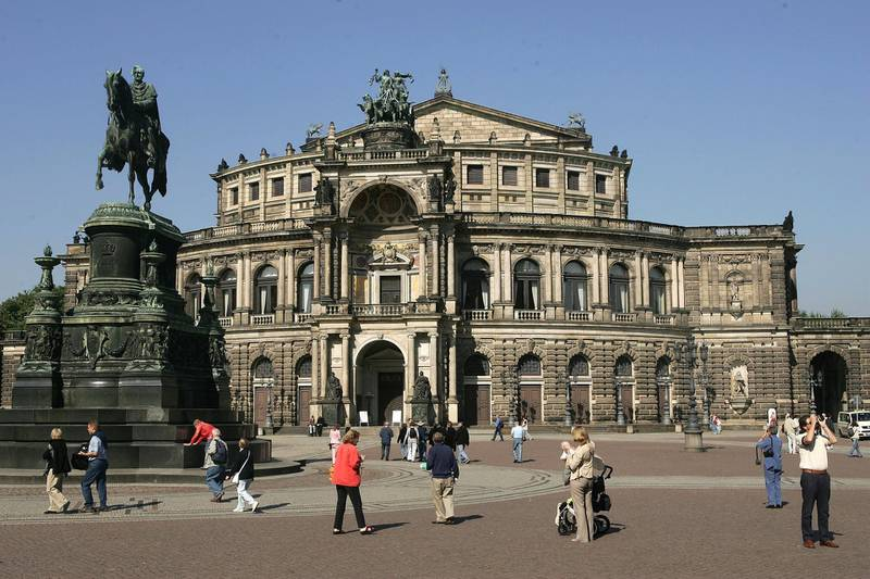 DRESDEN, GERMANY - SEPTEMBER 21: People walk by the Semper Opera House in Dresden's Old Town September 21, 2005 in Dresden, Germany. Due to the death of a political candidate shortly before Germany's September 18 national elections voting in Dresden's 160 voting district, which includes the Old Town, has been postponed until October 2. Though District 160 includes 219,000 eligible voters the result is unlikely to break the current post-election gridlock brought on by close results between the Social Democrats (SPD) and the Christian Democrats (CDU). The Dresden vote will nonetheless be watched closely by analysts as it could give one or the other party an argumentative advantage in coaltion negotiations.    (Photo by Sean Gallup/Getty Images)