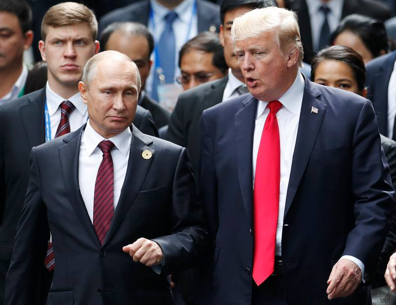 FILE - This Saturday, Nov. 11, 2017 file photo, shows U.S. President Donald Trump and Russia's President Vladimir Putin talking during the family photo session at the APEC Summit in Danang, Vietnam. When Trump meets Putin on Monday, July 16, 2018, the Syrian conflict will be the most immediately pressing issue on a wide-ranging agenda. (Jorge Silva/Pool Photo via AP, File)