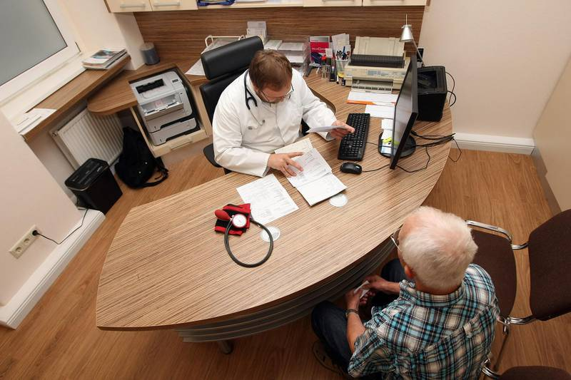 BERLIN, GERMANY - SEPTEMBER 05:  A doctor speaks to a patient as a sphygmomanometer, or blood pressure meter, lies on his desk on September 5, 2012 in Berlin, Germany. Doctors in the country are demanding higher payments from health insurance companies (Krankenkassen). Over 20 doctors' associations are expected to hold a vote this week over possible strikes and temporary closings of their practices if assurances that a requested additional annual increase of 3.5 billion euros (4,390,475,550 USD) in payments are not provided. The Kassenaerztlichen Bundesvereinigung (KBV), the National Association of Statutory Health Insurance Physicians, unexpectedly broke off talks with the health insurance companies on Monday.  (Photo by Adam Berry/Getty Images)