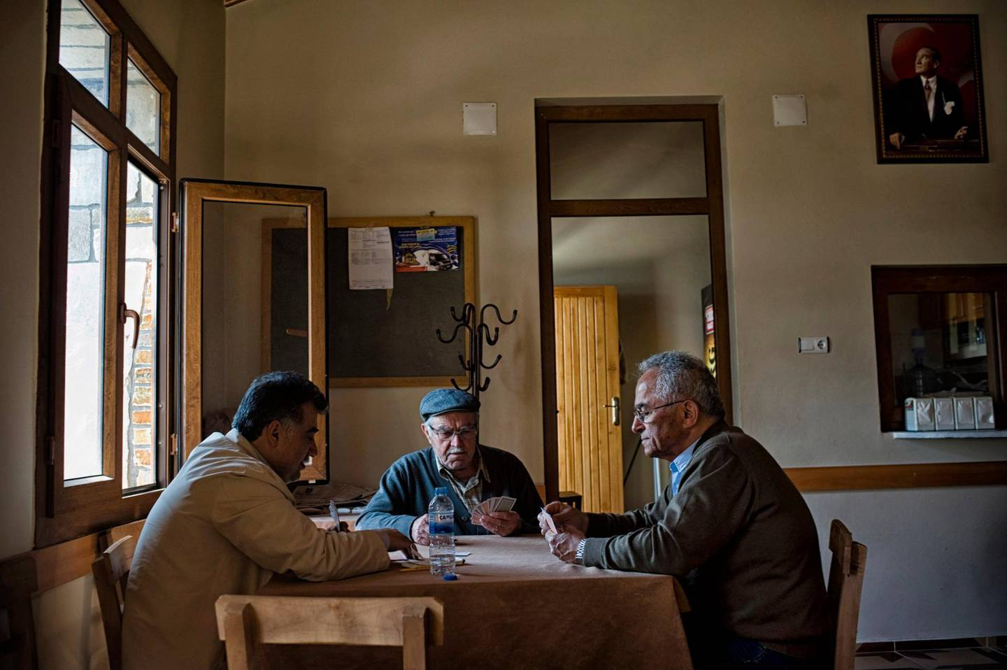 April 04, 2012.  Vakifli, Turkey - A group of Armenian men play cards in the local cafe in Vakifli, overlooked by a photograph of Kemal Ataturk.  Vakfili, a town of about 80 families near the border between Syria and Turkey, is the only Armenian village left in Turkey after the Genocide of 1915 and the pogroms that followed it. Courtesy Scout Tufankjian *** Local Caption ***  rv25ap-cover story-p1.jpg