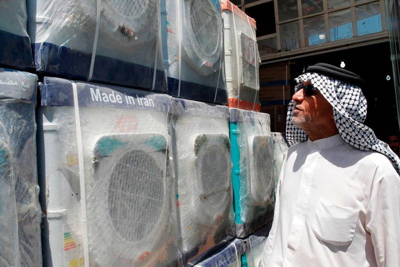 A customer looks at an Iranian-made washing machine at a store in the Iraqi capital, Baghdad on August 8, 2018. - Caught in the crossfire between its allies Tehran and Washington, Iraq could suffer the heaviest collateral damage from the renewed US economic sanctions which took effect against Iran on Wednesday. (Photo by SABAH ARAR / AFP)