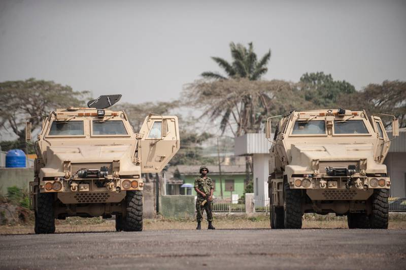 A Nigerian soldier stands between the 24 armoured vehicles donated by the United States to the Nigerian military at the Nigerian Army 9th Brigade Parade Ground in Lagos on January 7, 2016. - The U.S. government donated the vehicles to help fight Boko Haram, an extremist group whose six-year insurgency has killed over 17,000 people. (Photo by STEFAN HEUNIS / AFP)