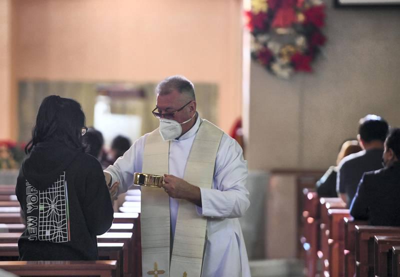 Abu Dhabi, United Arab Emirates - Father Stepan Lylak, from Ukraine hands out  the sacramental bread for communion during Christmas mass, at St. JosephÕs Cathedral, Mushrif. Khushnum Bhandari for The National