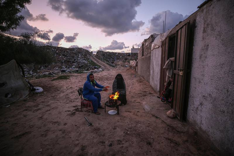 epa08149012 A couple warms themselves by a fire near their makeshift family house during cold weather in the south of Khan Younis Refugee Camp, Gaza Strip, 21 January 2020. More than 100 Palestinian families live in a devastating and an impoverished area, known as Nahr Al-Barid, and they do not have any source of income. Reports from human rights institutions state that more 70 percent of Gaza's population is living below the poverty line, set under international standards.  EPA/MOHAMMED SABER