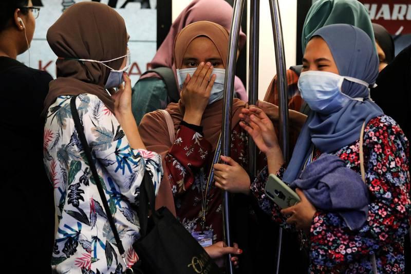 Passengers wear masks to prevent the outbreak of a new coronavirus in a Light Rail Transit train in Kuala Lumpur, Malaysia, January 31, 2020. REUTERS/Lim Huey Teng