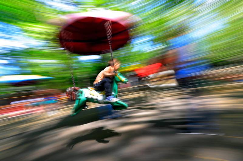 epa09201900 An image taken with a panning effect shows a boy riding a merry-go-round horse while its rotating at a Cismigiu Park playground that was opened for children, as the coronavirus alert situation ended in Bucharest, Romania, 15 May 2021. As SARS-CoV-2 coronavirus pandemic infection incidence dropped more than three days in a row under 1.5 percent per 1,000 inhabitants, Bucharest authorities decided that form May 15, people could walk in outside spaces without wearing a protection mask.  EPA/ROBERT GHEMENT PANNING EFFECT