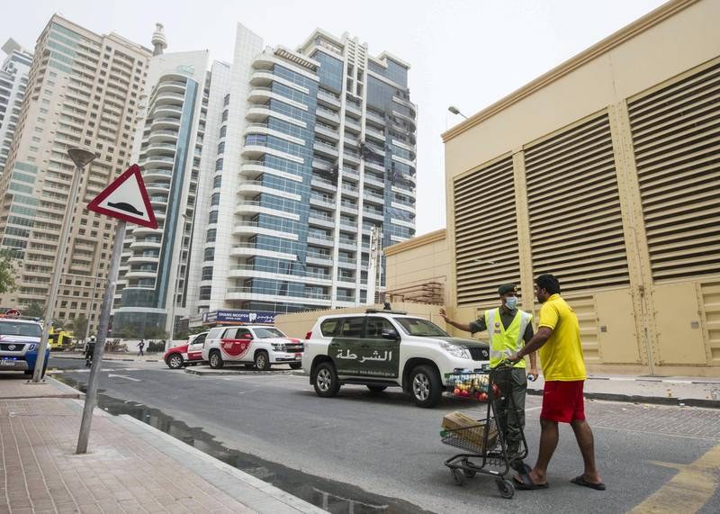 DUBAI, UNITED ARAB EMIRATES 13 MAY 2018 -A residence giving food to the a civil defence officer during the aftermath of the fire in Zen Tower in Marina, Dubai. Leslie Pableo for The National