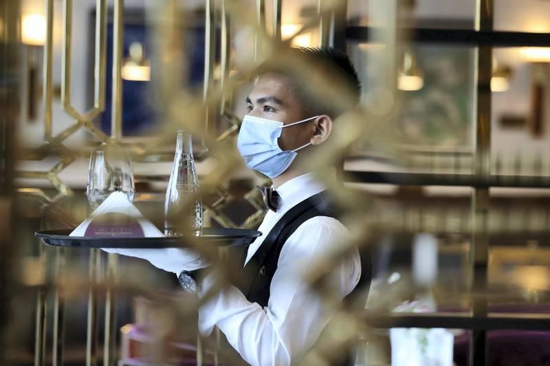 Dubai, United Arab Emirates - Reporter: N/A. News. Coronavirus/Covid-19. An employee at brings drinks to customers at Cafe Society in Dubai. Wednesday, November 11th, 2020. Dubai. Chris Whiteoak / The National