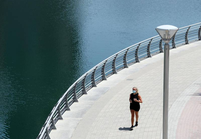 Dubai, United Arab Emirates - Reporter: N/A: Coronavirus. A lady exercises in the marina on the first morning where the government has eased restrictions on personal travel due to Covid-19. Friday, April 24th, 2020. Dubai. Chris Whiteoak / The National