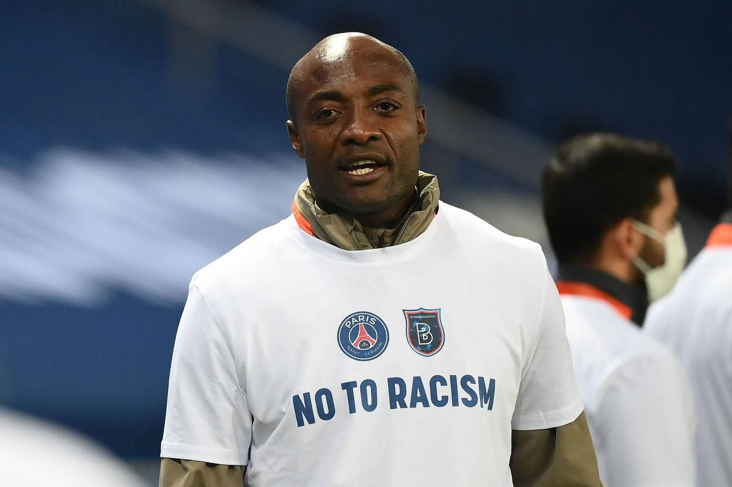 """TOPSHOT - Istanbul Basaksehir's Cameroonian assistant coach Pierre Webo, wearing a tshirt reading """"No to racism"""", looks on during warm-up before the UEFA Champions League group H football match between Paris Saint-Germain (PSG) and Istanbul Basaksehir FK at the Parc des Princes stadium in Paris, on December 9, 2020. The group game in Paris, which was goalless at the time, was suspended when both teams left the pitch on December 8, 2020 after a touchline argument erupted when the Romanian fourth official, Sebastian Coltescu, appeared to describe Basaksehir assistant coach Pierre Webo, a former Cameroon international player, as """"black"""", or """"negru"""" in Romanian and will resume on December 9 where it left off, in the 14th minute, with a different set of officials.  / AFP / FRANCK FIFE"""