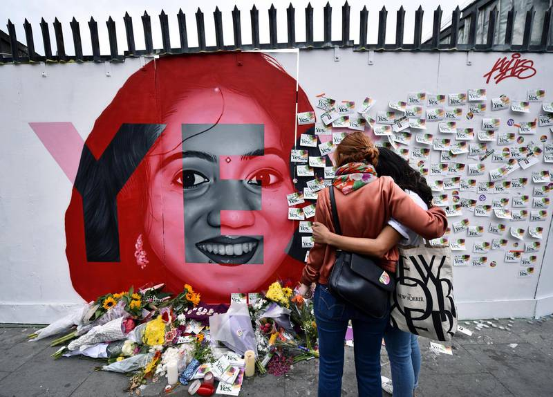 DUBLIN, IRELAND - MAY 26: Two women console one another as they look at written notes left on the Savita Halappanavar mural as the results in the Irish referendum on the 8th amendment concerning the country's abortion laws takes place at Dublin Castle on May 26, 2018 in Dublin, Ireland.  Savita Halappanavar who became the symbol of the Yes campaign to repeal the 8th amendment, died aged 32, due to complications following a septic miscarriage in Galway in 2012. Voters in Ireland went to the polls yesterday to decide whether to abolish or keep the 8th amendment, which makes it illegal for a woman to have an abortion in the country unless in circumstances where her life is at risk. Exit polls have indicated that the Yes vote has won by a landslide majority. (Photo by Charles McQuillan/Getty Images) *** BESTPIX ***