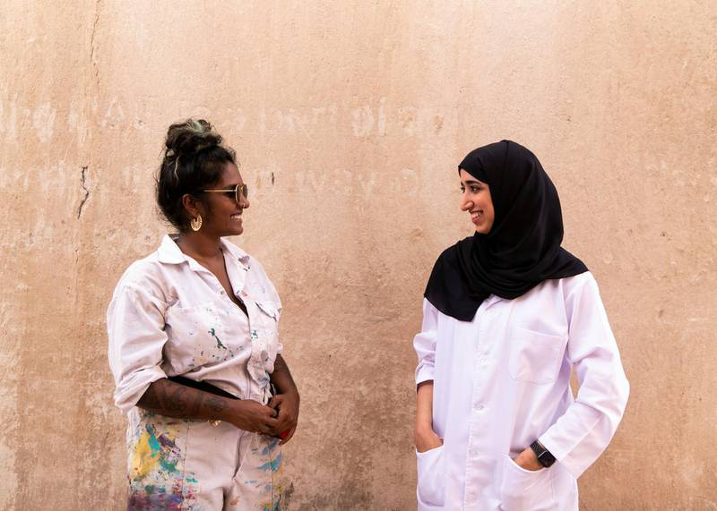 """DUBAI, UNITED ARAB EMIRATES. 25 JULY 2020. Artists Amna Basheer,left, and Reem Al Mazrouei work on their commission for Dubai Culture. They are painting a """"Hope mural"""" to celebrate the UAE Mars mission in Dubai's Al Fahidi district. (Photo: Reem Mohammed/The National)Reporter:Section:"""