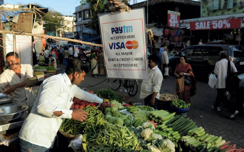 A sign advertising Indian electronic and cellpohne-based payment system PAYTM hangs at a roadside vegetable stall in Mumbai on February 25, 2017.  / AFP PHOTO / PUNIT PARANJPE