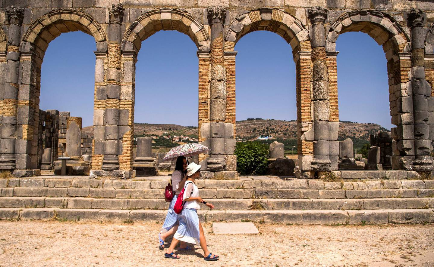 Tourists walk through the ruins of the ancient Roman site of Volubilis, near the town of Moulay Idriss Zerhounon in Morocco's north central Meknes region, on July 25, 2018. - Situated in the centre of a fertile plain at the foot of Mount Zerhoun, the towering remains of Morocco's oldest Roman site, Volubilis, were long neglected. But after decades of looting and decay, custodians of the now closely guarded ancient city are turning the page and attracting back tourists. (Photo by FADEL SENNA / AFP)
