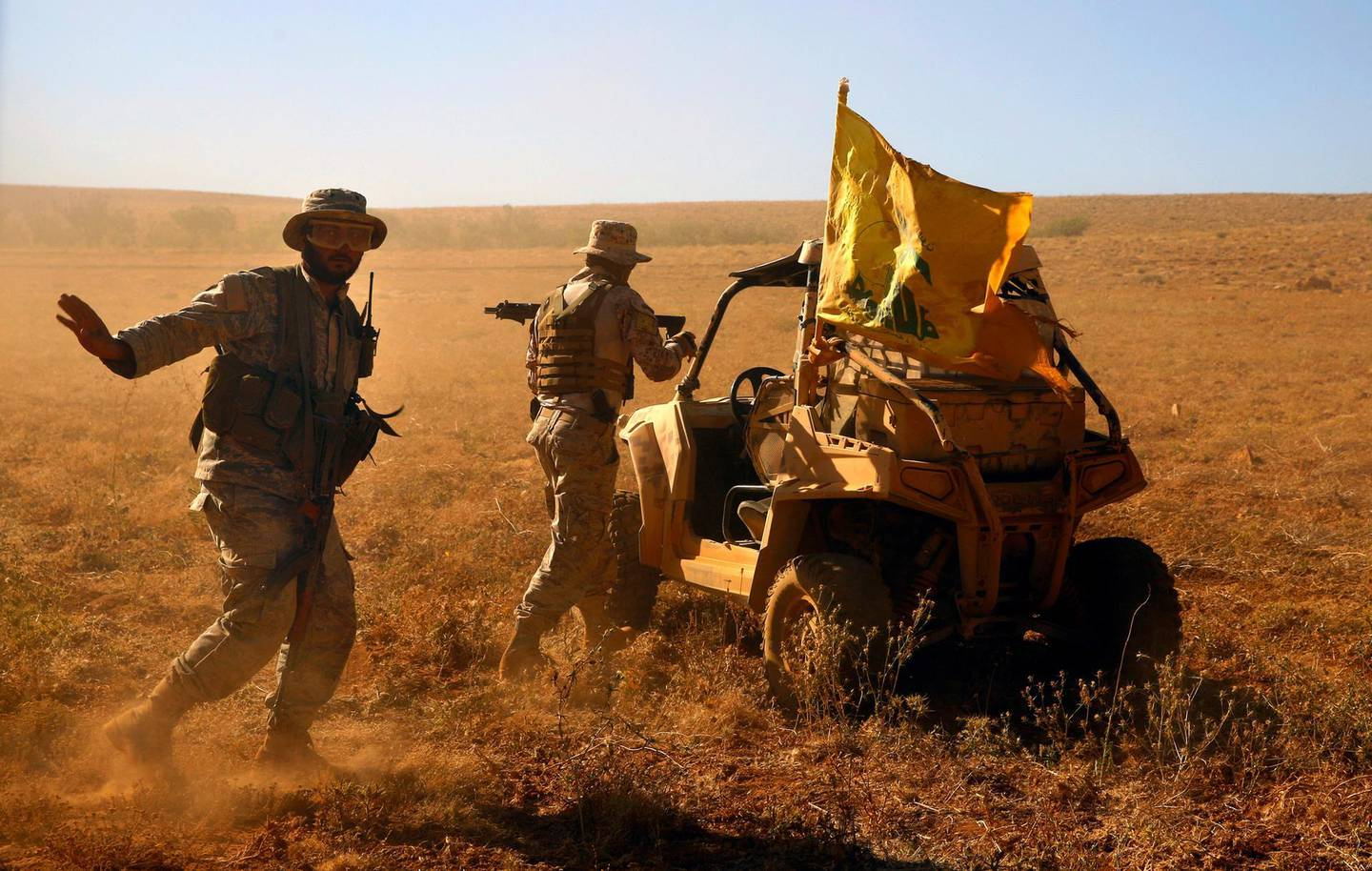 FILE - This July 29, 2017 file photo, Hezbollah fighters stand near a four-wheel motorcycle positioned at the site where clashes erupted between Hezbollah and al-Qaida-linked fighters in Wadi al-Kheil or al-Kheil Valley on the Lebanon-Syria border. The British government will make inciting support for Hezbollah a criminal offense as senior officials accused the Iran-backed organization of destabilizing the Middle East. (AP Photo/Bilal Hussein, File)