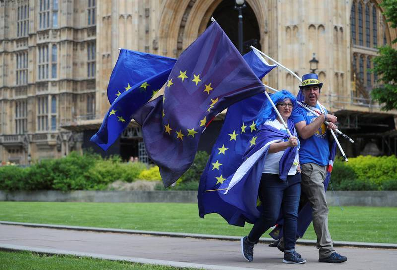 Two anti-Brexit protesters carry flags opposite the Houses of Parliament in London, Britain, May 10, 2018. REUTERS/Hannah McKay