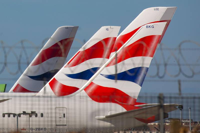 British Airways livery sits on the tail fins of passenger aircraft operated by British Airways, a unit of International Consolidated Airlines Group SA (IAG), sitting on the tarmac at London Heathrow Airport, London, U.K. on Monday, March 16, 2020. Airlines worldwide will shrink operations to only a trickle of flights, severing global links and putting hundreds of thousands of jobs at risk as they fight to preserve cash and survive the coronavirus pandemic. Photographer: Jason Alden/Bloomberg