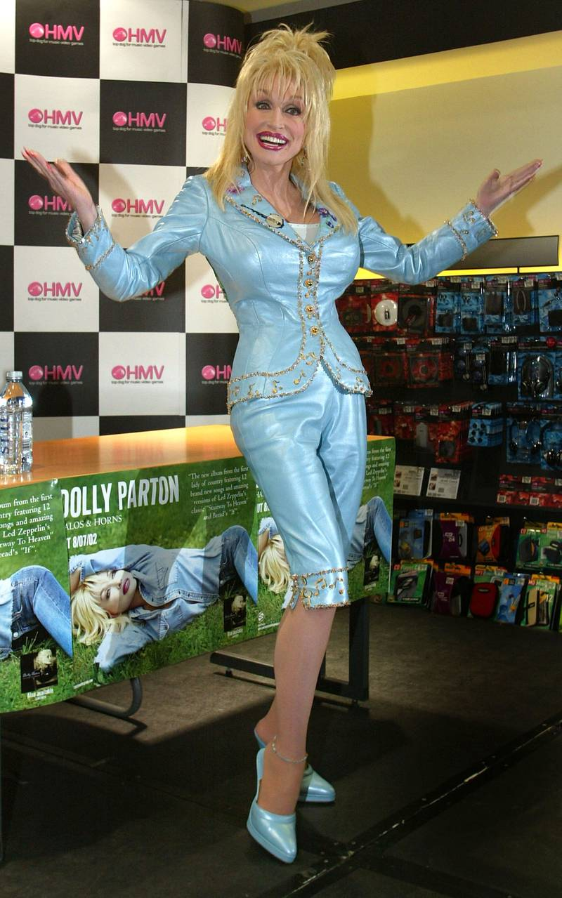 """LONDON - OCTOBER 8:  Singer Dolly Parton poses for photographers on October 8, 2002 at the Oxford Street HMV store in London, England.  Parton was at the store to sign copies of her recently released album, """"Halos and Horns,"""" which includes a cover of Led Zeppelin's """"Stairway to Heaven.""""  (Photo by Scott Barbour/Getty Images)"""