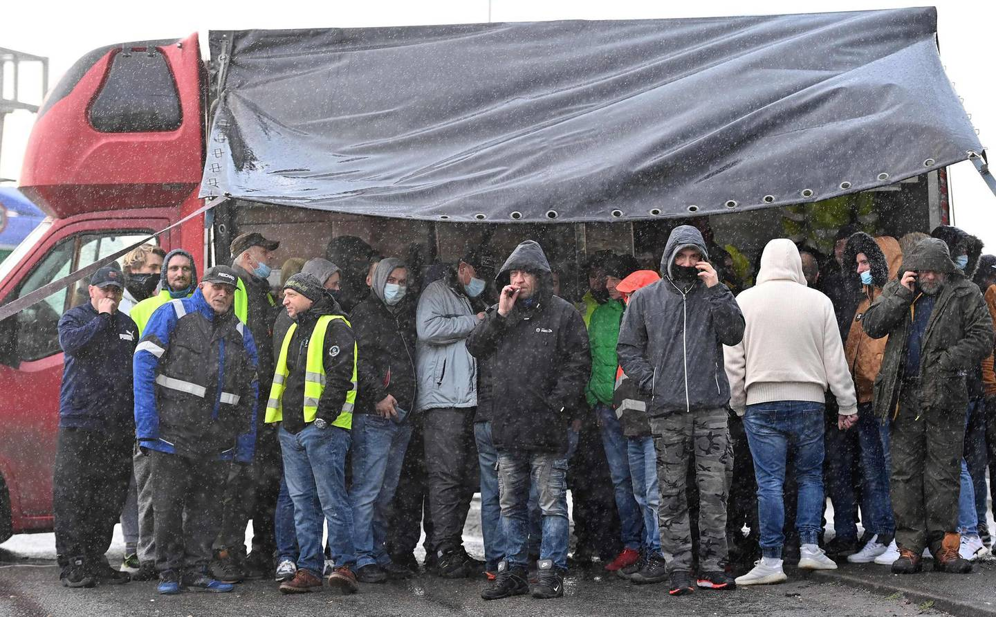 Drivers shelter from the rain by a lorry as they block the road by the entrance to the port in Dover, in Kent, south east England on December 23, 2020, as they are not being allowed to enter by police after the UK and France agreed a protocol to reopen the border to accompanied freight arriving in France from the UK.  France and Britain reopened cross-border travel after a snap 48-hour ban to curb the spread of a new coronavirus variant threatened UK supply chains. Accompanied frieght will now be allowed to cross the channel from the port of Dover but all lorry drivers will require a lateral flow test and a negative Covid-19 result before the travel.  / AFP / JUSTIN TALLIS