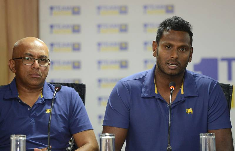 Sri Lanka's one-day and twenty20 cricket captain Angelo Mathews (R) addresses a press conference as coach Chandika Hathurusingha (L) looks on in Colombo on January 9, 2018. Sri Lanka on January 9 announced Angelo Mathews would return as skipper for limited-overs cricket ahead of the 2019 World Cup, just six months after the allrounder stepped down from the post. / AFP PHOTO / LAKRUWAN WANNIARACHCHI