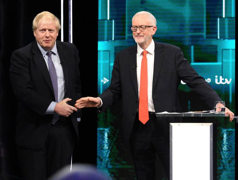 In this photo issued by ITV, Boris Johnson, left, and Jeremy Corbyn, shake hands during their election head-to-head debate live on TV, in Manchester, England, Tuesday, Nov. 19, 2019.  Prime Minister Boris Johnson and Jeremy Corbyn are set to go head-to-head in their first live televised debate Tuesday evening, as the UK prepares for a General Election on Dec. 12. (ITV via AP)