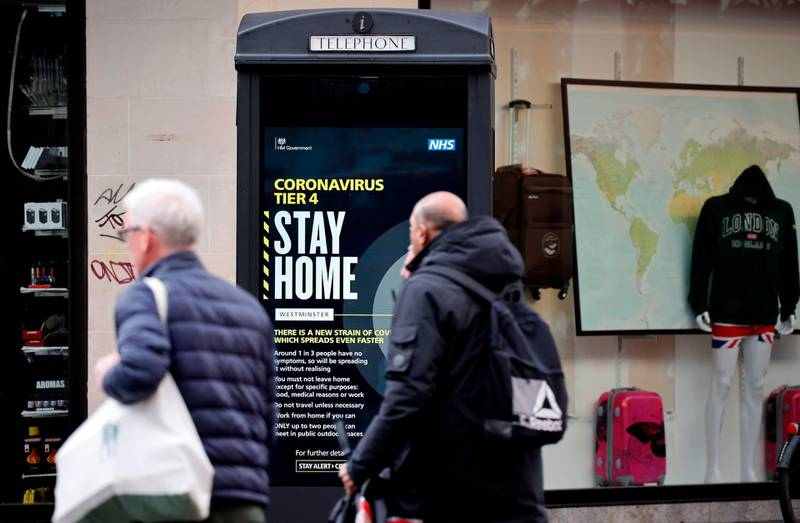 """Pedestrians walk past a COVID-19 Tier 4 information sign in central London on December 23, 2020. Britain's public health service urged Prime Minister Boris Johnson on Wednesday to extend the country's Brexit transition period or risk pushing hospitals already struggling with coronavirus """"over the edge"""" in the event of a no-deal departure from the EU single market. / AFP / Tolga Akmen"""