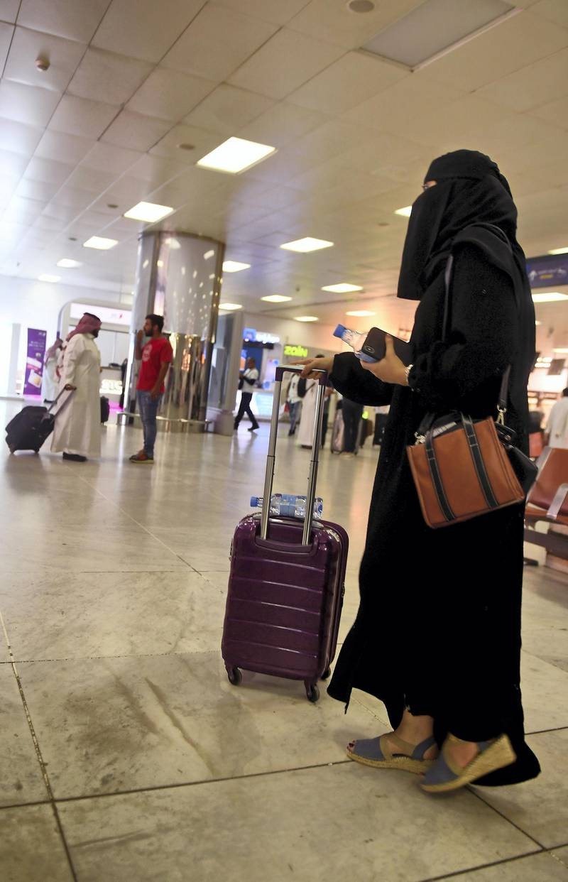"""A Saudi woman rolls her suitcase at the departure hall of the Jeddah Airport on August 6, 2019. - Saudi Arabia's easing of travel restrictions on women was hailed in the kingdom last week as a historic leap for gender equality, but it also drew anger from hardliners backing contentious male """"guardianship"""" rules. The Muslim kingdom announced it was effectively allowing women over the age of 21 to obtain passports and travel abroad without securing the permission of their """"guardians"""" -- husband, father or other male relatives. (Photo by - / AFP)"""