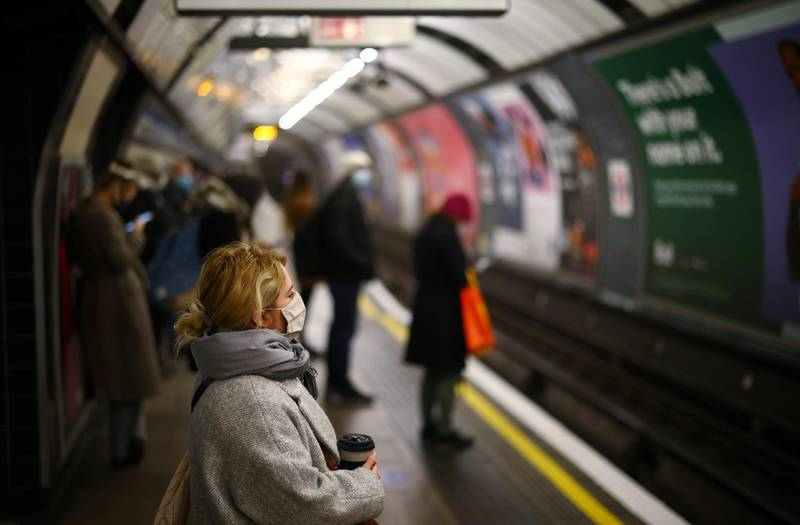 A woman wearing a face mask and holding a cup looks on at the Vauxhall tube station amid the coronavirus disease (COVID-19) outbreak, in London, Britain January 12, 2021. REUTERS/Henry Nicholls