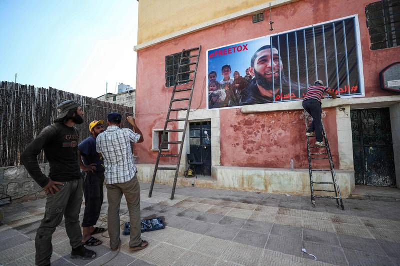 Men fix up a banner on the side of a building calling for the release of Tauqir Sharif, a self-described aid worker stripped of his British nationality and detained by Hayat Tahrir al-Sham (HTS) jihadists, at the premises of his charity organisation in the town of Atme in Syria's rebel-held northwestern Idlib province, on July 1, 2020. According to his supporters, Tauqir Sharif, 33, was detained on June 22 by the Hayat Tahrir al-Sham group dominant in the northwest Syria region of Idlib, while HTS has not issued any statement on his detention. Sharif, whose father is Pakistani, hails from Chingford in East London and first arrived in Syria in 2012, according to the Live Updates from Syria organisation with which he worked. Britain stripped him of his British nationality in 2017 over allegedly being aligned with an Al-Qaeda-aligned group it did not name, but he has denied those charges. / AFP / OMAR HAJ KADOUR