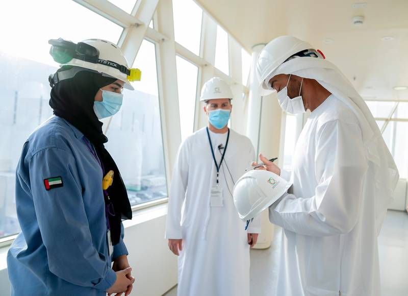 AL DHAFRA, ABU DHABI, UNITED ARAB EMIRATES - June 11, 2020: HH Sheikh Mohamed bin Zayed Al Nahyan, Crown Prince of Abu Dhabi and Deputy Supreme Commander of the UAE Armed Forces (R) signs a helmet of a member of the Emirates Nuclear Energy Corporation, during the inspection of the Barakah Peaceful Nuclear Energy Plants, in Barakah. Seen with HE Mohamed Al Hammadi, CEO Emirates Nuclear Energy Corporation (ENEC) (C).  ( Mohamed Al Hammadi / Ministry of Presidential Affairs ) ---