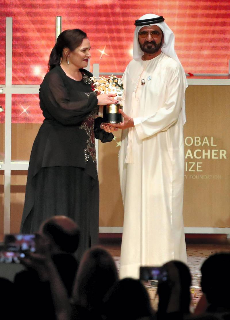 """British teacher Andria Zafirakou receives the """"Global Teacher Prize"""" from Sheikh Mohammed bin Rashid al-Maktoum, Vice-President and Prime Minister of the UAE and Ruler of Dubai during an award ceremony in Dubai on March 18, 2018. - Zafirakou who  was among ten finalists chosen from 179 countries, won one million dollars of prize money. (Photo by KARIM SAHIB / AFP)"""