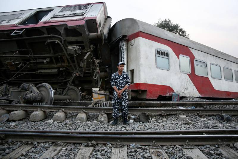 A member of Egyptian security forces stands guard before an overturned passenger carriage at the scene of a railway accident in the city of Toukh in Egypt's central Nile Delta province of Qalyubiya on April 18, 2021. - The train accident north of Cairo on April 18 left 11 people dead and 98 others injured, after it derailed off its tracks heading northwards from the capital Cairo, the health ministry said, in the latest railway disaster. Eight carriages derailed off the tracks as the train headed to Mansoura, about 130 kilometres north of Cairo. (Photo by Ayman Aref / AFP)