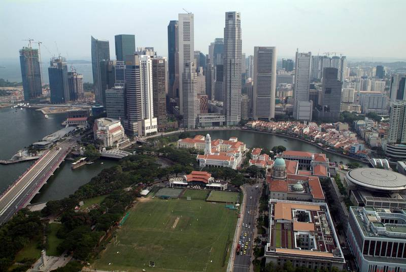 SINGAPORE - 2009/08/01: A view over the Padang Cricket Ground, the Singapore River and the Central Business District in Singapore. Much of the colonial-era architecture (seen with red roofs) was built between the 1820's and 1870's and has been maintained and restored under National heritage laws. Most of the buildings in the CBD have been built within the last 20 years.This view is from an Executive Floor room at the Swissotel The Stamford Hotel, one of Southeast Asia's tallest hotels. (Photo by Leisa Tyler/LightRocket via Getty Images)