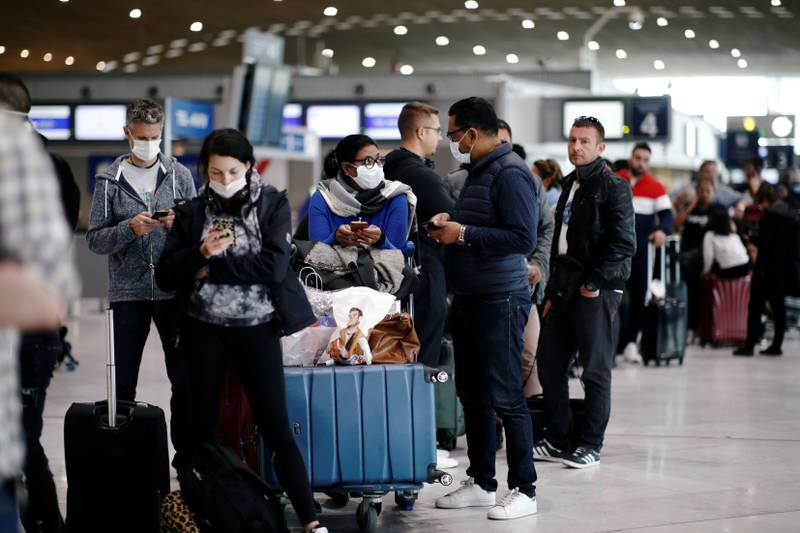Masked travellers stand in line with luggage before getting to the Air France ticket counter at Paris Charles de Gaulle airport, following the coronavirus disease (COVID-19) outbreak, in Roissy-en-France, France March 16, 2020. REUTERS/Benoit Tessier