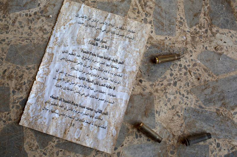 QARAQOSH, IRAQ - NOVEMBER 08: Bullet casings are seen next to a sheet of Christian writings on the ground of the  burnt and destroyed St Mary al-Tahira church on November 8, 2016 in Qaraqosh, Iraq. The NPU is a military organization made up of Assyrian Christians and was formed in late 2014 to defend against ISIL. Qaraqosh, a largely Assyrian City just 32km southeast of Mosul was taken by ISIL in August, 2014 forcing all residents to flee, the town was largely destroyed with all of the churches burned or heavily damaged. The town stayed under ISIL control last week when it was liberated during the Mosul Offensive.  (Photo by Chris McGrath/Getty Images)