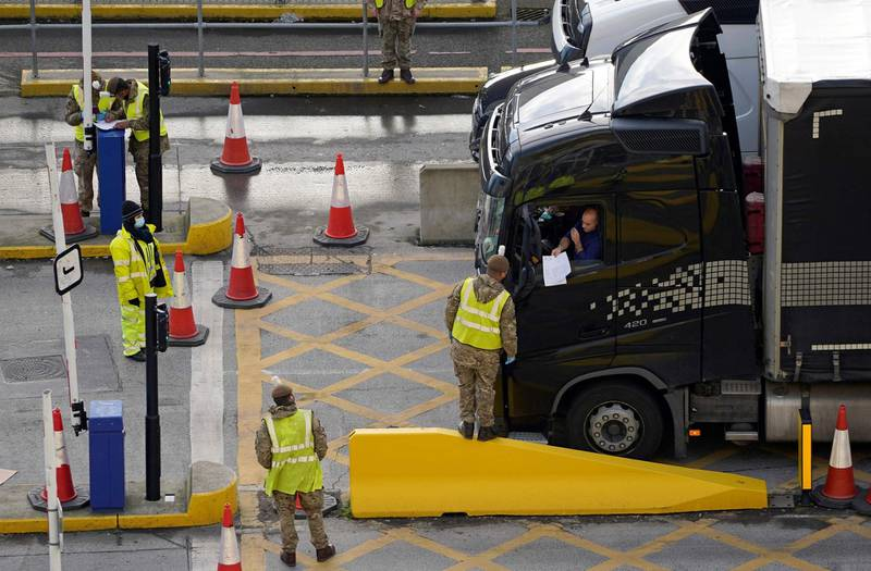 (FILES) In this file photo taken on December 25, 2020 A lorry driver shows their credentials to a member of the British Army, as they enter the Port of Dover, in Dover on the south-east coast of England, as the COVID-19 testing of drivers queueing to depart from the ferry terminal to Europe continues. Truck drivers coming from the UK no longer need a PCR or antigen test to enter France, according to a decree published on March 25, 2021. / AFP / Niklas HALLE'N