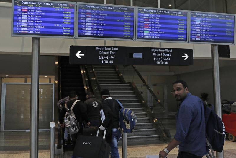 A small number of passengers take the direction of gates before travelling from the Lebanese capital Beirut's Rafiq Hariri international airport with disinfectant, to limit the spread of the Covid-19 coronavirus, on March 18, 2020. (Photo by ANWAR AMRO / AFP)